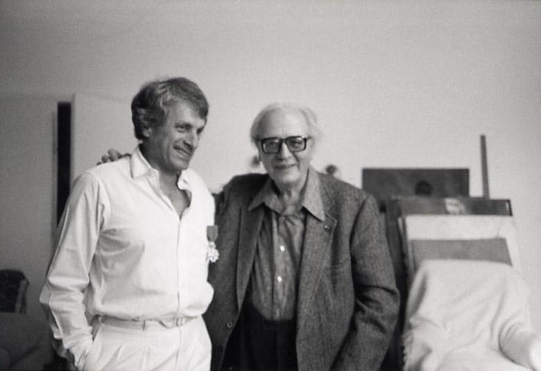 Olivier Messiaen remettant les insignes de chevalier de la légion d'honneur à Iannis Xenakis dans son appartement de la Rue Chaptal, vers 1977.